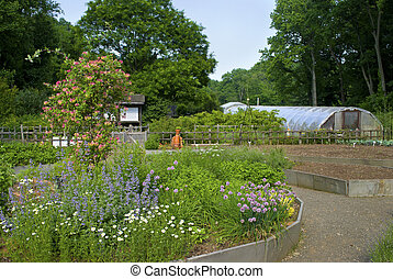 Greenhouse and Garden - A view of an organic garden and...