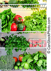 Greens, fruits and vegetables in fridge. Vegan, raw, healthy lifestyle concept