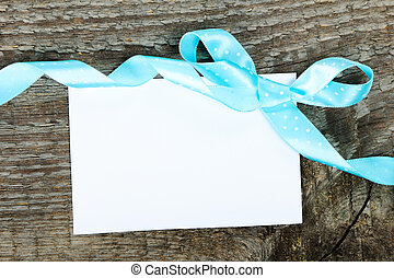 Empty greeting card with ribbon and bow on wooden background