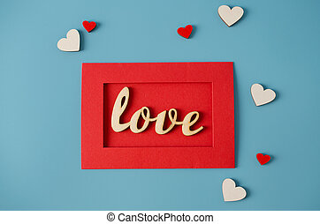 Greeting card for Valentine's Day. Red envelope with a love message and wooden heards on blue background.