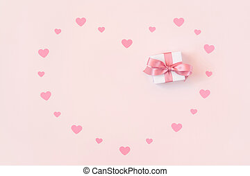 Greeting card for Valentine's Day. Small confetti hearts and a gift on a pink background. Valentines day concept. Space for text.