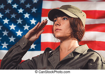 Greeting card for Veterans Day, Memorial Day, Independence Day. Portrait of a female soldier saluting, against the background of the American flag. Side view