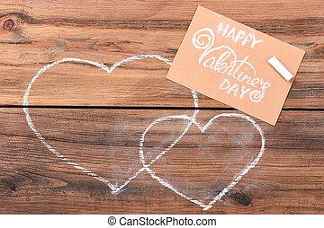 Greeting card near drawn hearts.