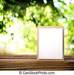 Greeting card on the wooden table over green tree leaves