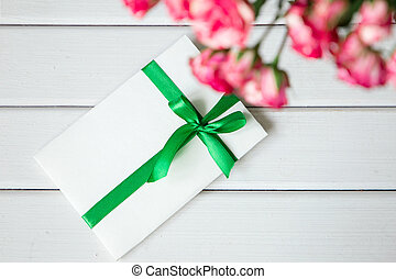 greeting card with pink roses on wooden background. Top view