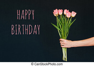 Greeting card with the inscription happy birthday. Bouquet of pink Tulip flowers in a woman's hand