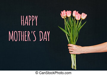 Greeting card with the inscription happy mother's day. Bouquet of pink Tulip flowers in a woman's hand