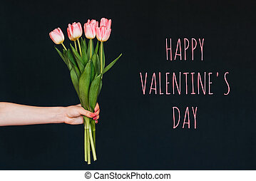Greeting card with the inscription happy valentine's day. Bouquet of pink Tulip flowers in a woman's hand
