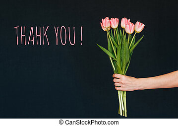 Greeting card with the inscription thank you. Bouquet of pink Tulip flowers in a woman's hand