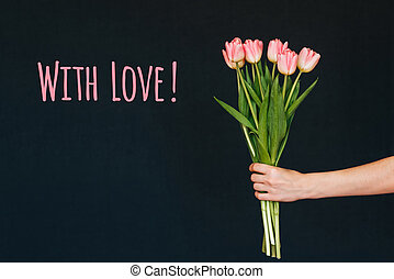 Greeting card with the inscription with love. Bouquet of pink Tulip flowers in a woman's hand