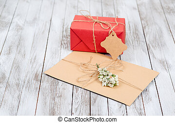 Greeting letter and gift box with tag on wooden background.