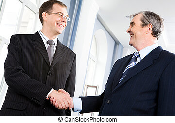 Greeting - Portrait of businessmen shaking hands greeting ...