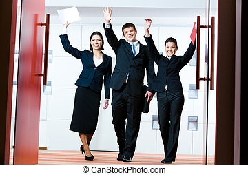 Portrait of successful business group standing at the door of conference hall with raised hands greeting their partners