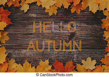 Greeting text Hello Autumn on wooden background with frame of maple leaves