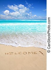 greetings welcome beach spell written on sand Caribbean ...