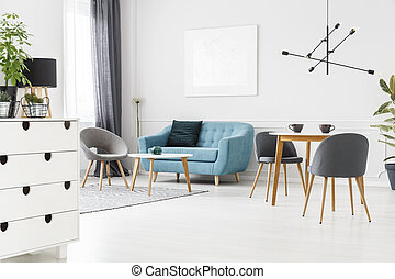 Grey and blue open space - Grey armchair at table near blue...
