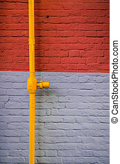 brick wall with yelllow tube