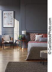 Grey and orange hotel bedroom - Grey armchair near lamp on...