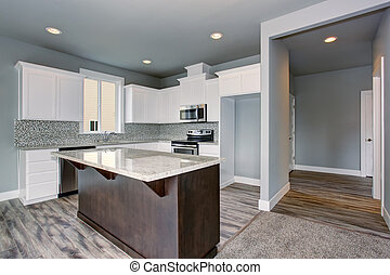 Grey and white kitchen interior with dark brown kitchen island.