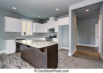 Grey and white kitchen interior with dark brown kitchen island.