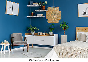 Grey armchair in blue bedroom