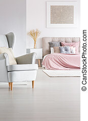 Grey armchair in trendy bedroom