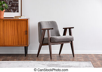 Grey armchair next to wooden cabinet with plant in grey retro living room interior. Real photo