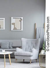 Grey armchair next to wooden table in living room interior with posters above couch. Real photo