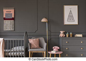 Grey armchair with pink pillow between bed and cabinet in child's bedroom interior. Real photo