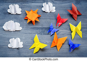 Grey background with paper multicolored butterflies, sun and clouds