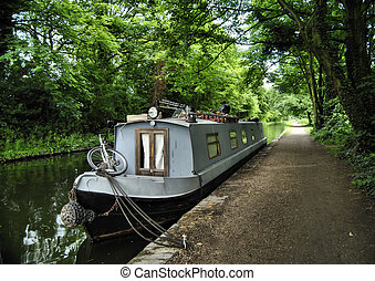 Grey Barge - Gray topped barge moored beside canal tow path;...