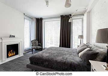 Grey bedroom with fireplace and bed