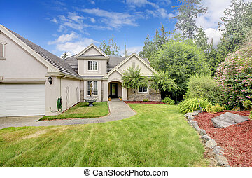 Grey beige large nice house exterior with summer landscape.