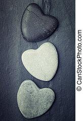 Grey, black, white zen hearts shaped rock on a tile background
