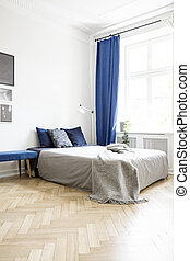 Grey blanket on bed in bright bedroom interior with lamp and navy blue drapes at window. Real photo