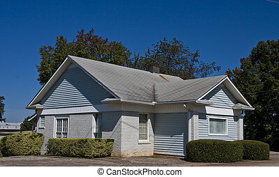 Grey Brick Bungalow - A small grey brick bungalow under a...