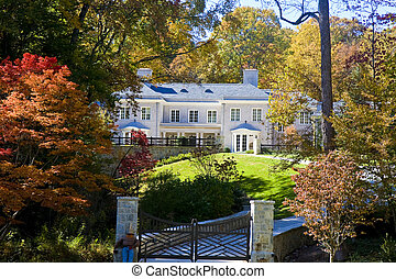 A gray brick mansion on a grassy hill inside an iron fence