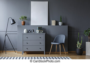 Grey cabinet between black lamp and chair in living room interior with mockup of poster. Real photo