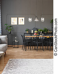 Grey carpet in apartment interior with black chairs at dining table and posters on the wall. Real photo