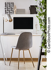 Grey chair at desk with desktop computer and lamp in modern white workspace interior. Real photo