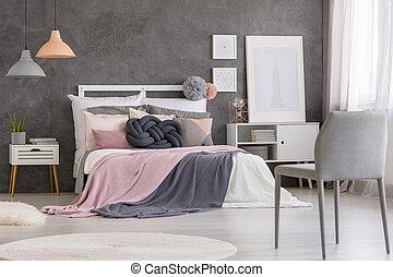 Grey chair in pink bedroom