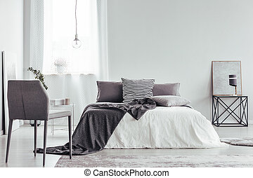 Grey chair in white bedroom