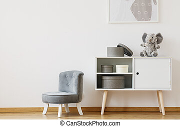 Grey chair next to white shelf with boxes and plush toy in...
