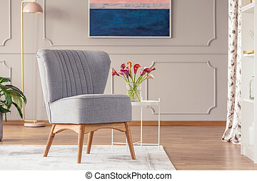 Grey chair on carpet next to table with flowers in elegant living room interior with lamp. Real photo
