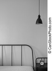 grey color metal line head bed with vintage alarm clock on black night side table and industrial look pendant