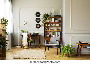 Grey comfortable armchair in vintage stylish interior with plants, book, and vinyls on the wall