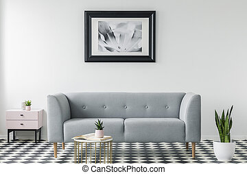 Grey couch between cabinet and plant in simple living room interior with poster and table. Real photo