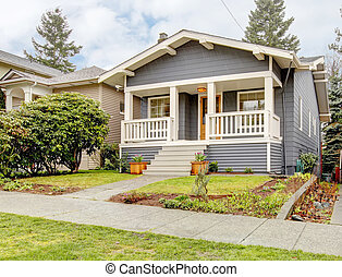 Grey craftsman style house with white porch.