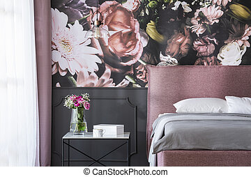 Grey cushions on pink bed next to table with flowers in...