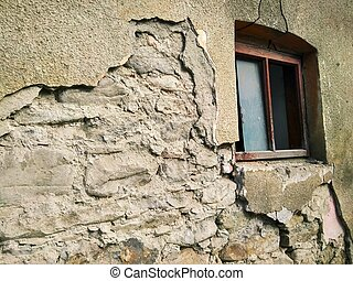 dilapidated wall of an old house with a window